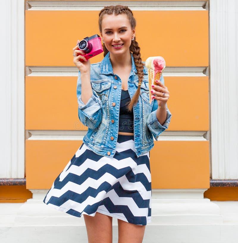 摆在有桃红色葡萄酒照相机和多彩多姿的冰淇凌的一件夏天礼服和牛仔布夹克的美丽的时兴的女孩 O 库存图片