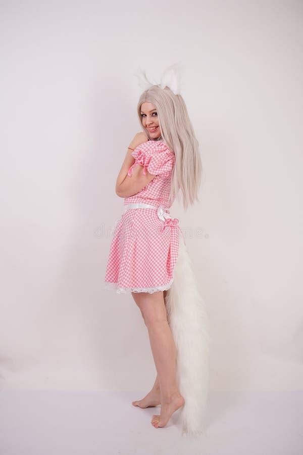 摆在有毛皮猫耳朵和一条长的蓬松尾巴的一件迷人的格子花呢披肩巴法力亚礼服的逗人喜爱的白肤金发的女孩在S的白色背景 图库摄影
