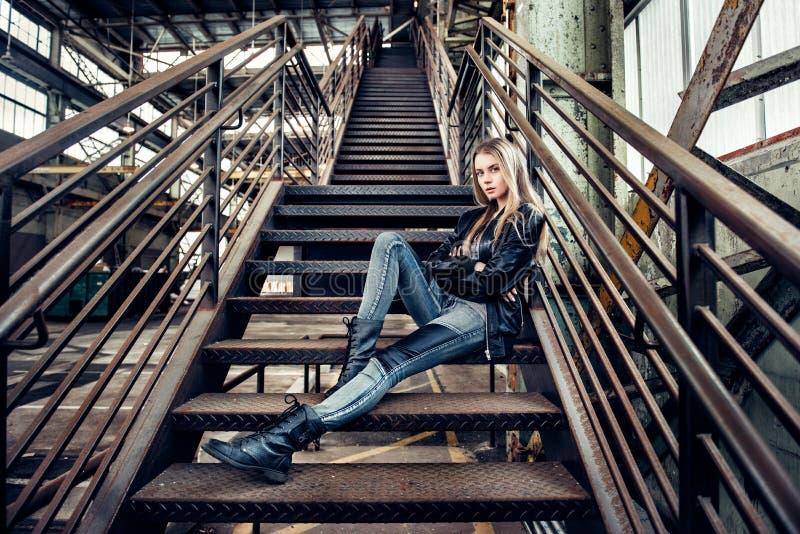 摆在有皮夹克、黑鞋子和时兴的牛仔裤的美丽的妇女佩带的偶然成套装备 摆在工业pla的女孩 免版税库存照片