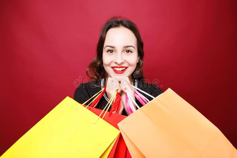 摆在有纸购物袋的演播室的可爱的妇女 免版税图库摄影
