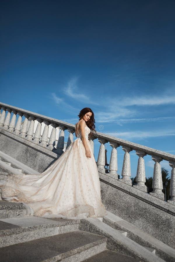 摆在有蓝色夏天天空的台阶的白色鞋带婚纱的美丽,性感和时兴的深色的女孩在 免版税库存照片