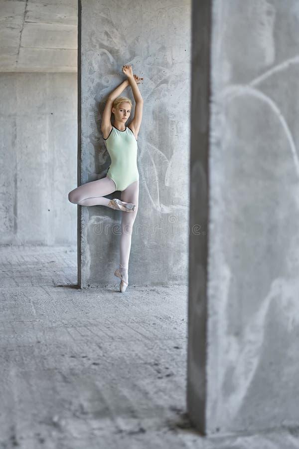 摆在未完成的大厦的芭蕾舞女演员 免版税库存照片