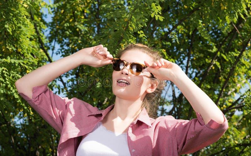 摆在本质上的太阳镜的可爱的少妇和紧贴到玻璃手 免版税库存照片