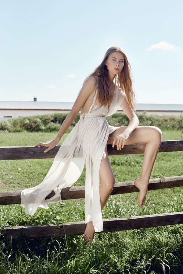摆在村庄的一件轻的白色礼服的性感的年轻女人在老房子附近 有一个完善的图的女孩在背景 免版税库存照片