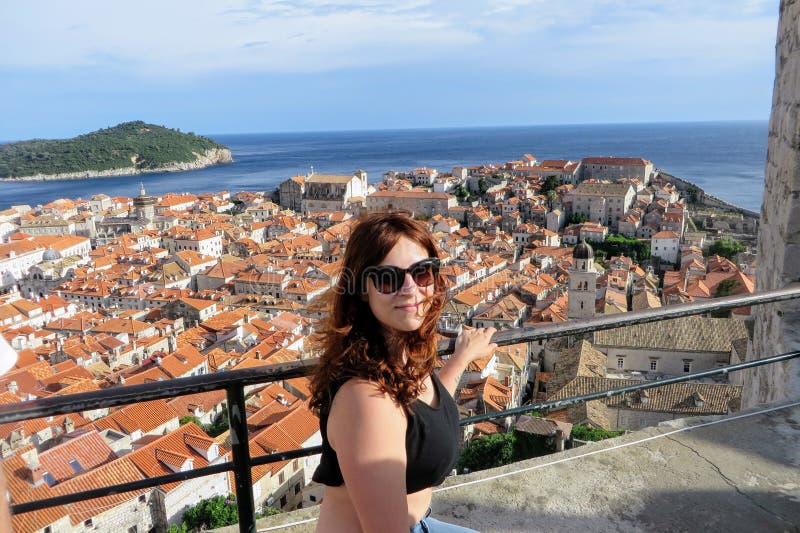 摆在杜布罗夫尼克顶部墙壁的一个年轻俏丽的女性游人俯视杜布罗夫尼克,克罗地亚老镇  库存照片