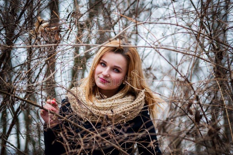 摆在树枝下的女孩画象 免版税图库摄影