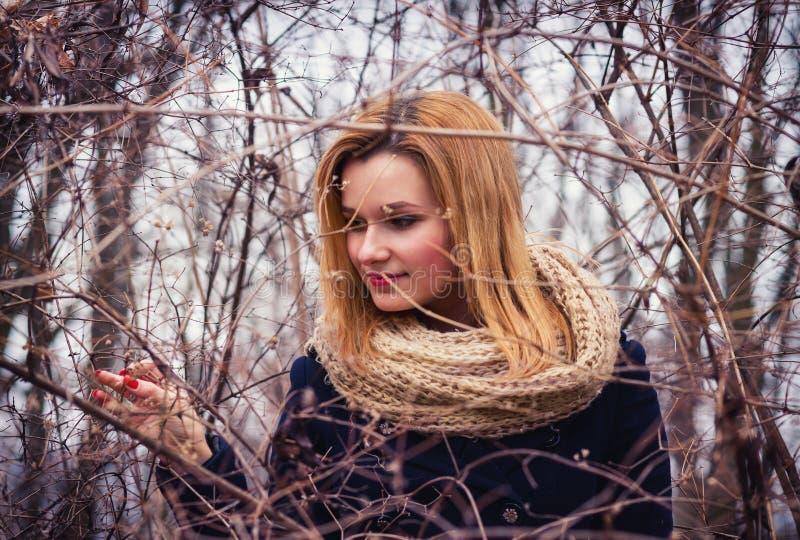 摆在树枝下的女孩画象 免版税库存图片