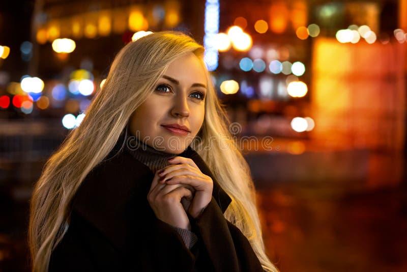 摆在根据晚上城市的女孩 图库摄影