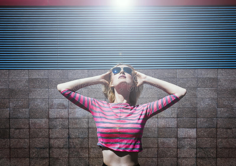 摆在桃红色镶边女衬衫和太阳镜的白肤金发的女孩,查寻与被投掷的头和手  天,室外 免版税库存图片