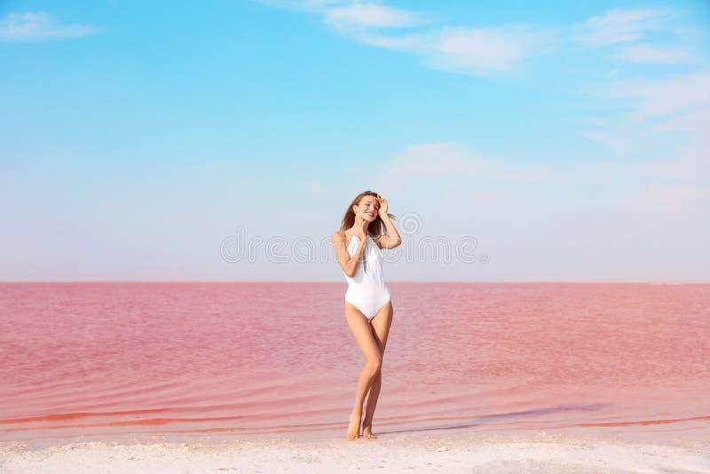 摆在桃红色lak附近的泳装的美丽的妇女 库存照片