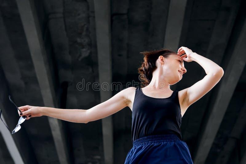 摆在桥梁下的女孩,穿戴在黑,现代建筑学 图库摄影