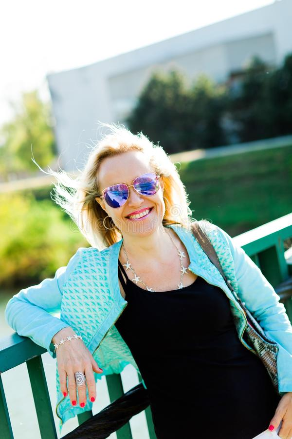 摆在桥梁的可爱的白肤金发的妇女 库存图片