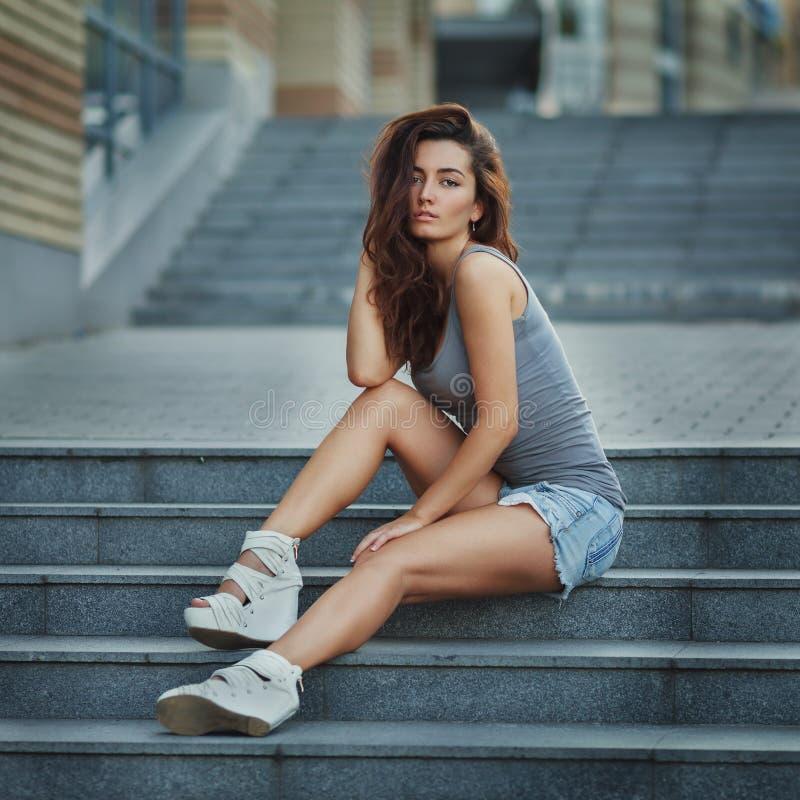 摆在楼梯的俏丽的少女室外生活方式画象,佩带在都市背景的行家都市样式 免版税库存照片