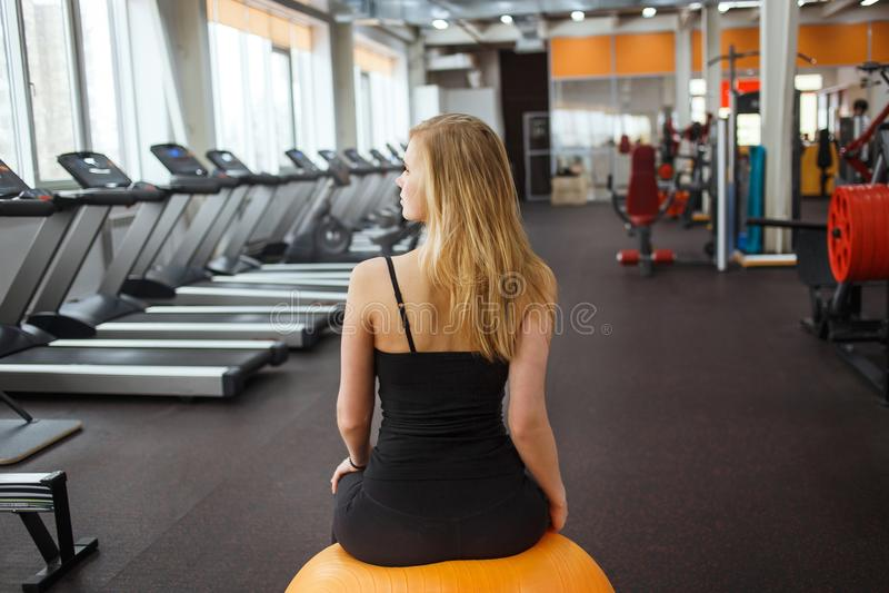 摆在橙色球的健身房的年轻运动的妇女反对在背景的很多踏车 库存图片