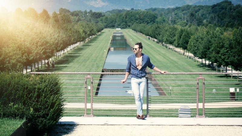 摆在欧洲豪华庭院里的英俊的肌肉人 免版税库存图片