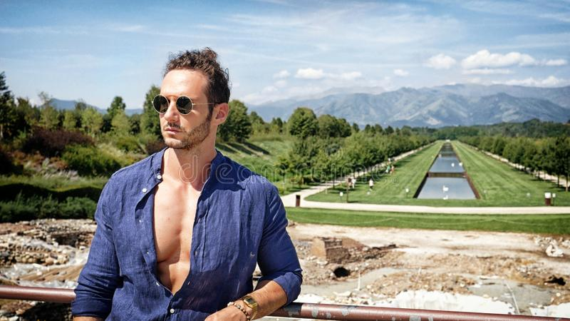 摆在欧洲豪华庭院里的英俊的肌肉人 库存照片