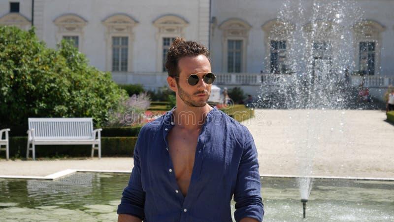 摆在欧洲豪华庭院里的英俊的肌肉人 免版税库存照片