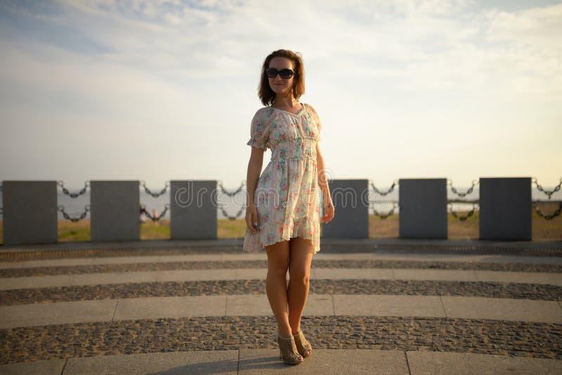 摆在正方形的礼服的逗人喜爱的女孩 日落 库存照片