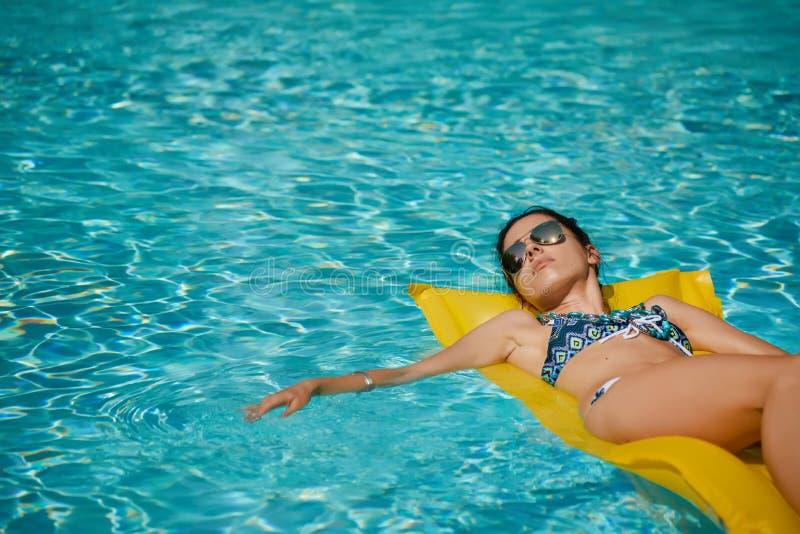 摆在水池的夏天的年轻俏丽的时尚妇女身体与分类 免版税图库摄影
