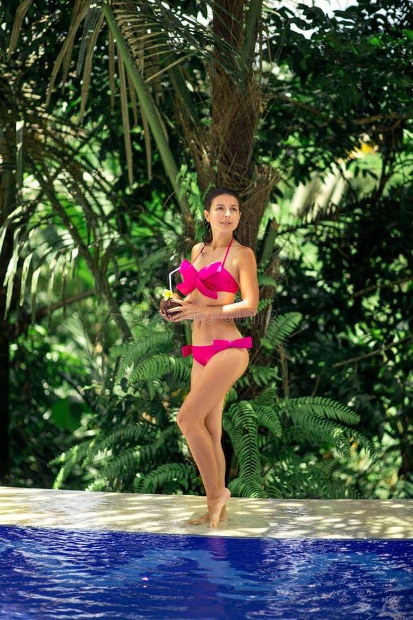 摆在水池的桃红色泳装的女孩 免版税图库摄影