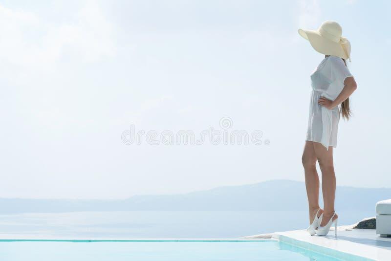 摆在水池附近的长袍和宽充满的帽子的可爱的女孩 库存图片