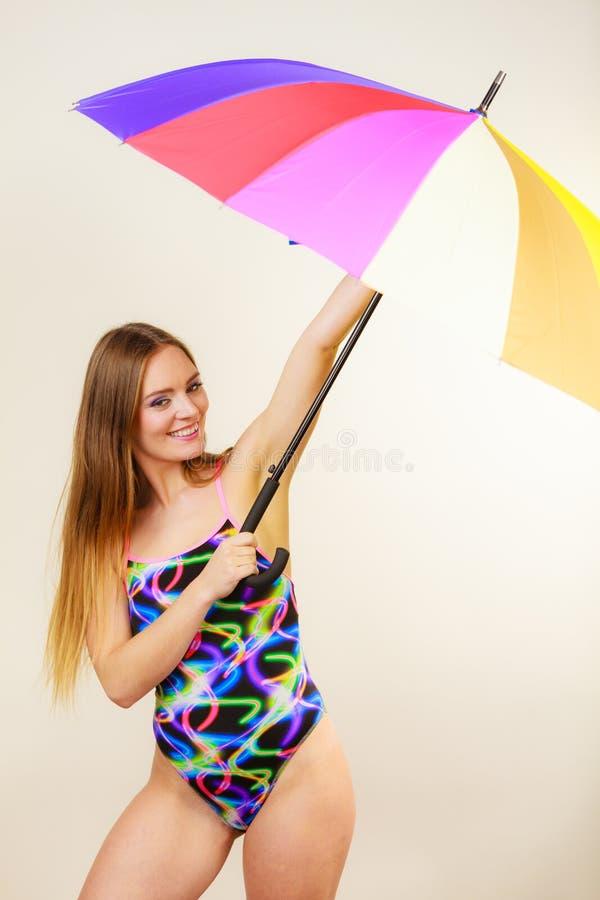 摆在泳装和五颜六色的伞的愉快的妇女 库存照片