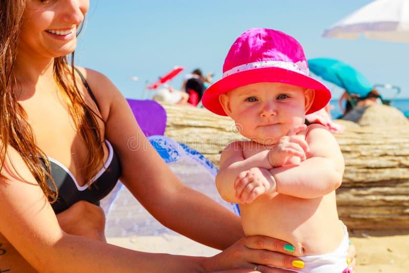 摆在泳装的母亲和婴孩 免版税库存图片
