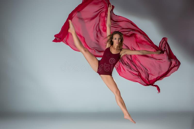 摆在浅灰色的演播室背景的红色泳装的年轻美丽的妇女舞蹈家 库存照片