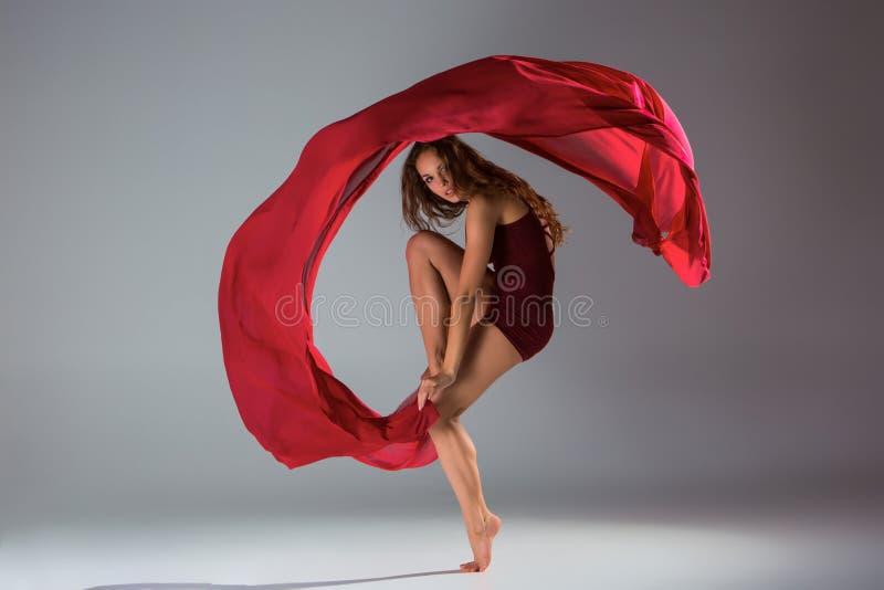 摆在浅灰色的演播室背景的红色泳装的年轻美丽的妇女舞蹈家 免版税图库摄影