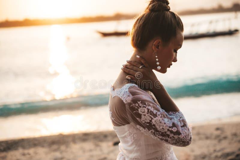 摆在海后的海滩的美丽的新娘在日落 免版税库存图片
