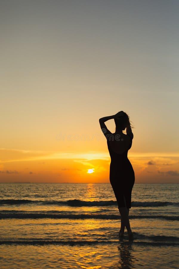 摆在海洋的妇女剪影背面图在日落期间 库存图片