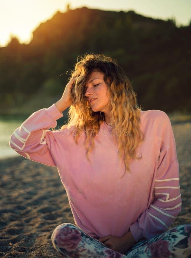 摆在海滩的白肤金发的女孩 免版税库存图片
