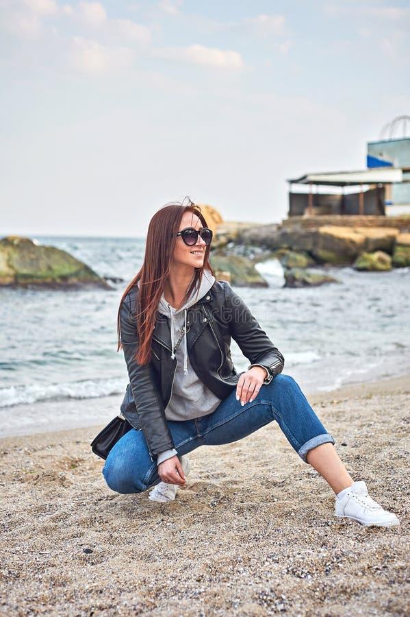 摆在海滩的美丽的年轻红头发人妇女靠近海洋 免版税库存照片