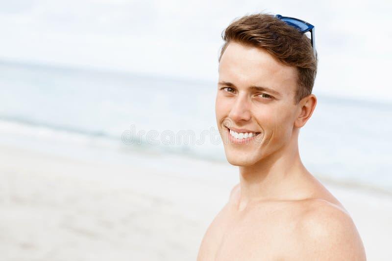 摆在海滩的英俊的人 图库摄影