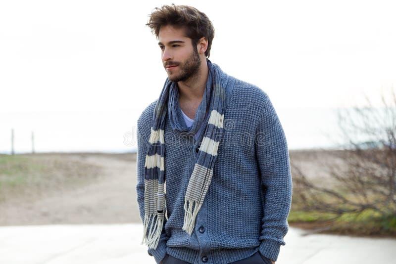 摆在海滩的一个冷的冬天的英俊的年轻人 免版税图库摄影