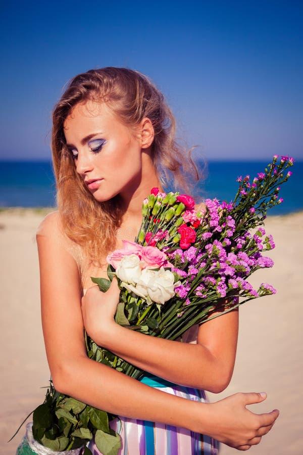 摆在海滩的一个美丽的年轻白肤金发的女孩 免版税图库摄影