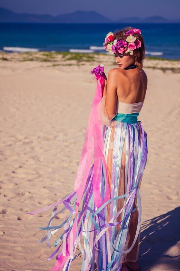 摆在海滩的一个美丽的年轻白肤金发的女孩 库存照片