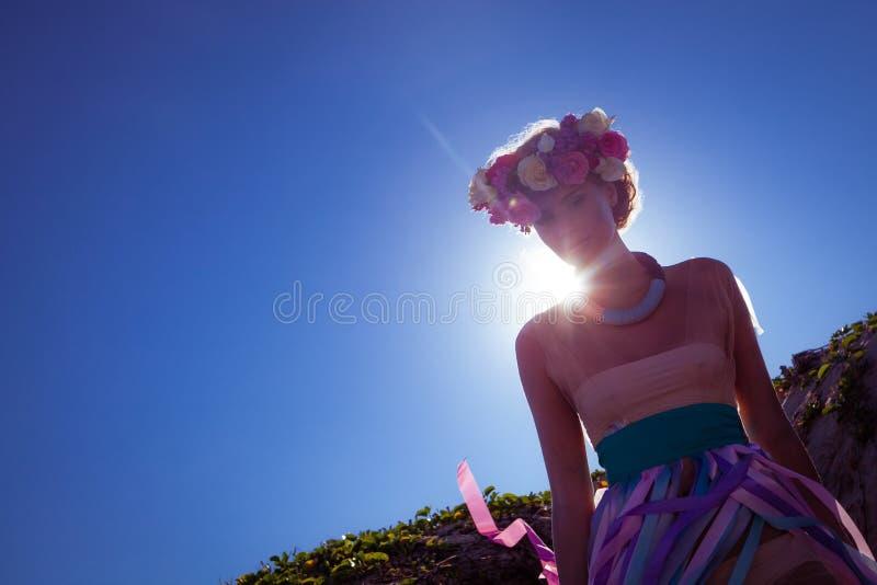摆在海滩的一个美丽的年轻白肤金发的女孩 免版税库存照片