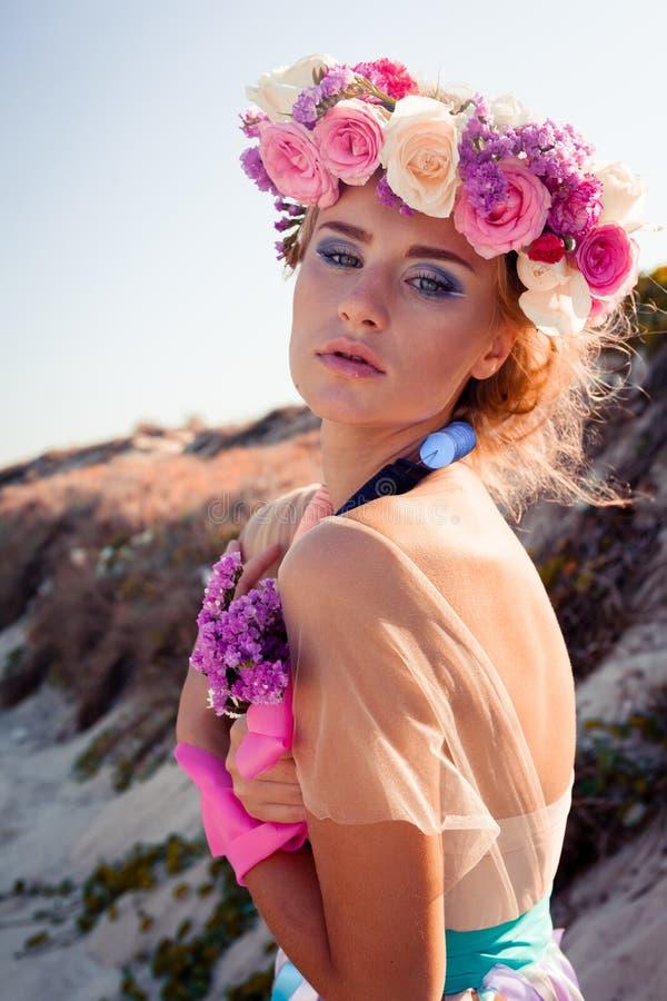 摆在海滩的一个美丽的年轻白肤金发的女孩 免版税库存图片