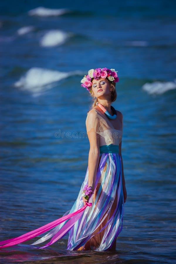 摆在海滩的一个美丽的年轻白肤金发的女孩 图库摄影