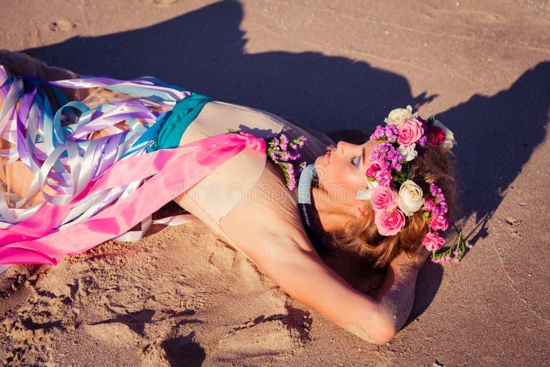 摆在海滩的一个美丽的年轻白肤金发的女孩 库存图片