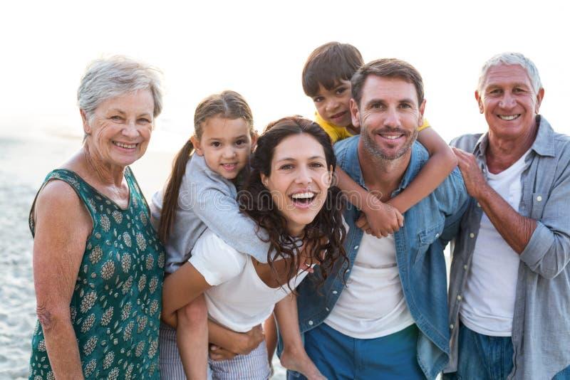 摆在海滩的愉快的家庭 库存照片
