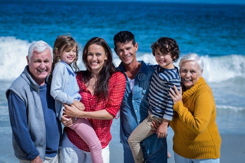 摆在海滩的愉快的家庭 免版税库存图片