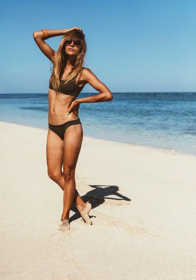 摆在海滨的比基尼泳装的肉欲的女性模型 库存照片