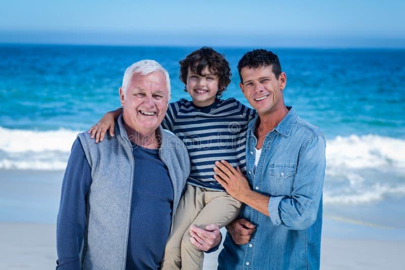 摆在海滩的男性家庭成员 免版税库存照片