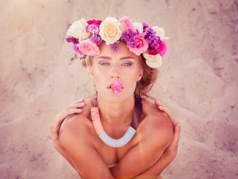 摆在海滩的花圈的年轻美丽的白肤金发的新娘 图库摄影