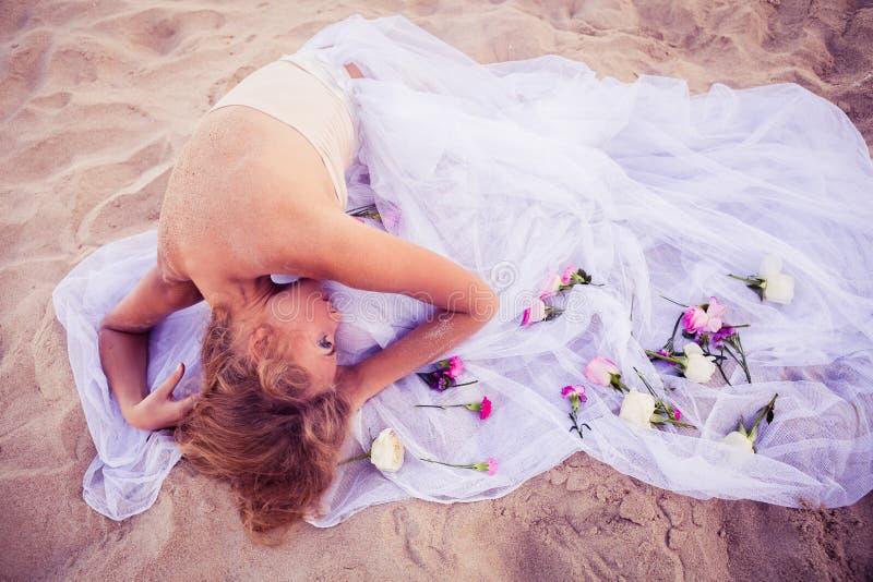 摆在海滩的花圈的年轻美丽的白肤金发的新娘 免版税库存照片