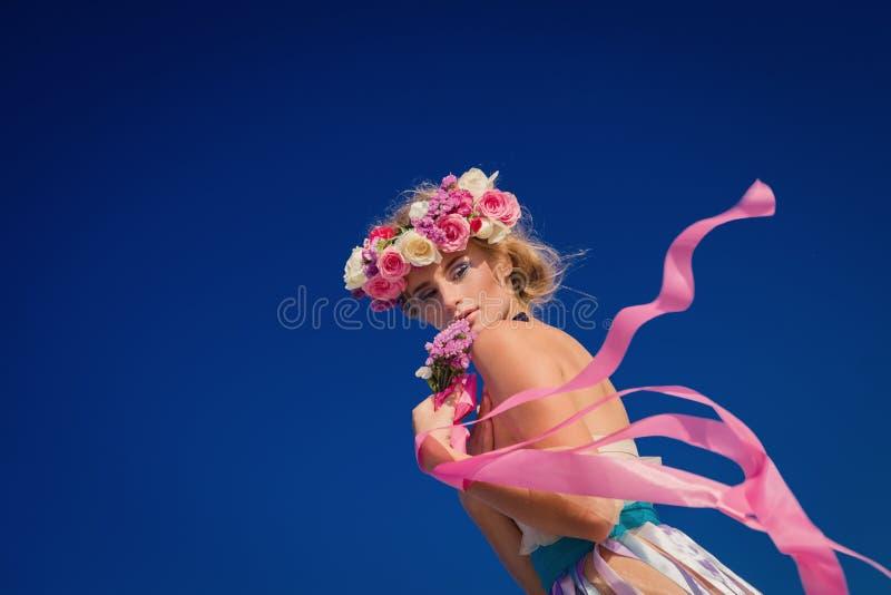 摆在海滩的花圈的年轻美丽的白肤金发的新娘 免版税图库摄影