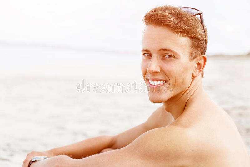 摆在海滩的英俊的人 库存照片
