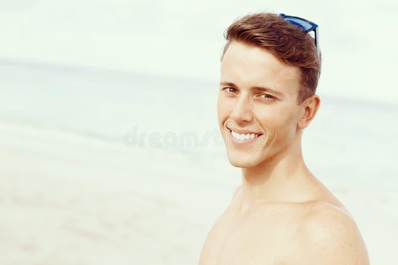 摆在海滩的英俊的人 免版税图库摄影